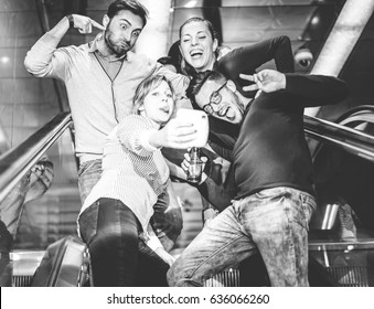 Happy friends taking photos with instant camera on escalator in underground - Group of young people taking a selfie making funny faces for social media - Black and white edit - Focus on the left man