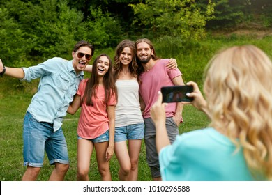 Happy Friends Taking Photos On Phone In Nature. Portrait Of Young Smiling People In Colorful Clothes Having Fun And Laughing On Weekend Outdoors. High Quality Image.