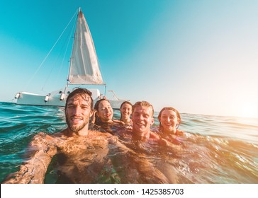 Happy friends taking a selfie with action cam inside the ocean with sail boat in background - Young people having fun swimming in the sea - Focus on left man face - Travel and youth concept