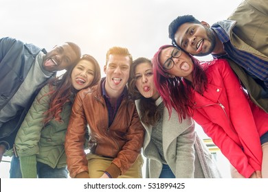 Happy friends taking selfie photo making funny faces with back sun light - Young multiracial people having fun together outdoor - Multi race friendship concept - Warm filter