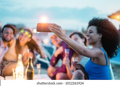 Happy friends taking selfie with smartphone at beach party outdoor - Young people having fun at kiosk bar drinking champagne - Soft focus on mobile cell phone - Youth lifestyle and vacation concept
