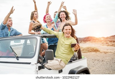 Happy friends taking selfie with smartphone in desert on convertible 4x4 car - Travel people having fun together in excursion tour - Friendship and vacation concept - Focus on man's face with phone