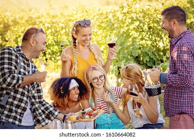 Happy friends tasting wine in vineyard - Young people enjoying time together outside at countryside - Youth friendship and wine tours concept