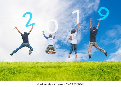 Happy friends team work and adult people jumping congratulation graduation in Happy New year 2019.  Freedom lifestyle business team jump as part of Number 2019 on  green meadow, blue sky background.