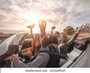 Happy friends with their hands up having fun in cabriolet car on vacation - Young people laughing and enjoying together during travel road trip - Youth holidays lifestyle concept