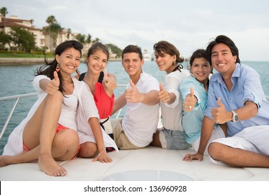 Happy friends with thumbs up in a yacht enjoying the summer