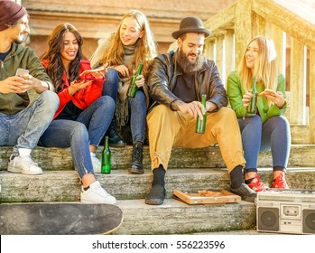 Happy friends toasting beer and eating pizza take away - Young people having fun in city center listening music at sunset - Party,trends and friendship concept - Warm filter - Focus on middle guys