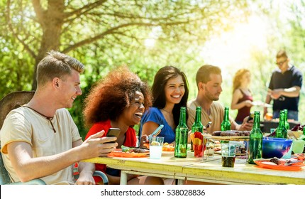 Happy friends toasting beer and having barbecue outdoor with back sun light - Young people having fun in bbq party - Friendship,summer,fun and dinner concept - Focus on left man face - Warm filter