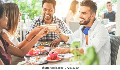 Happy friends toasting cappuccino at bar cafeteria - Young trendy people enjoying breakfast eating drinking coffee - Friendship and morning break concept - Focus on center hands glasses - Warm filter