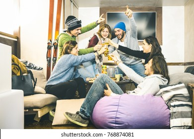 Happy friends toasting and drinking beer at after ski pub lodge - Friendship concept with cheerful people having fun at bar restaurant resort with snow equipment - Winter season travel experience