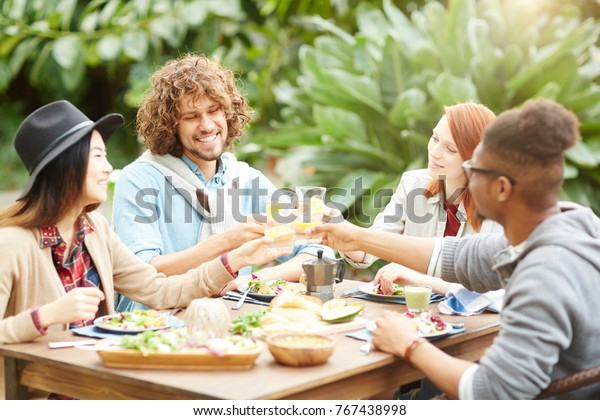 Happy friends toasting with homemade lemonade over served table by breakfast