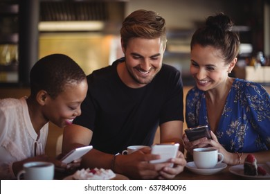 Happy friends using mobile phone while having breakfast in restaurant