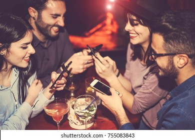 Happy friends using mobile phone and having fun with cocktails in a jazz bar - Young people addicted to new smartphone technology - Concept of youth, cellphone and lifestyle - Focus on right male hand