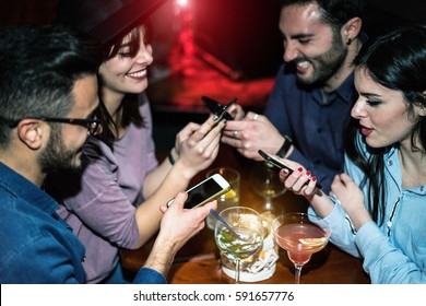 Happy friends using mobile phones in jazz cocktail bar - Young people are addicted to new trends technology - Online social concept - Focus on right girl face - Unfiltered photo made with flash