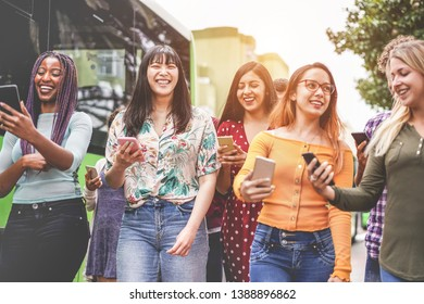 Happy friends using smartphones at bus station - Young students people having fun with technology trends after school outdoor - Friendship, university and trasports app concept - Focus on indian girl