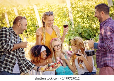 Happy friends in vineyard tasting wine  - Young multi-ethnic people enjoying time together outside at countryside - Youth friendship and wine tours concept