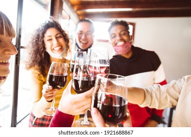 Happy friends wearing protective face masks toasting red wine at restaurant - New normal friendship concept with young people having fun at home party - Focus on glasses