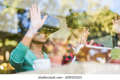 Happy friends wearing virtual reality goggles in modern coworking space - Window reflection view from outside - Smartphones using with vr headset - Focus on african girl mouth glasses - Tech concept