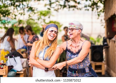 happy friendship couple of woman young and mature ladies with hippy clothes and dress have fun together dancing and hugging each other. beautiful adults enjoying a colored festival
