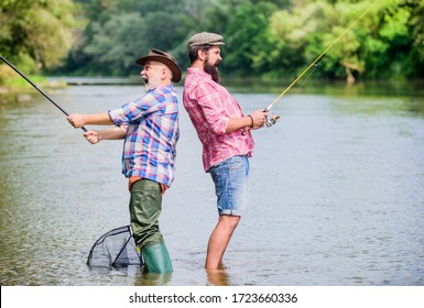 happy friendship. hobby and sport activity. Trout bait. father and son fishing. two happy fisherman with fishing rod and net. summer weekend. mature men fisher. male friendship. family bonding.