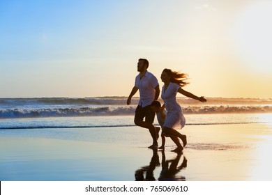 Happy full family - father, mother, baby son have fun together, child run with splashes by water pool along sunset sea surf on black sand beach. Travel lifestyle, parents with kids on summer vacation.