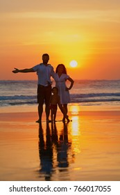 Happy full family - young father, mother, baby son have fun together on black sand beach with sea surf on sunset sky with sun background. Travel lifestyle, parents with kids on summer tropical holiday