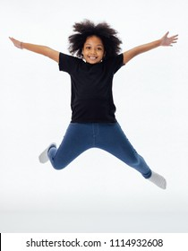 Happy and fun African American black kid jumping with hands raised isolated over white background