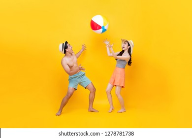 Happy fun Asian couple playing beach ball together in colorful yellow background