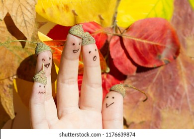 Happy fun autumn acorn family against colorful leaves fall background concept
