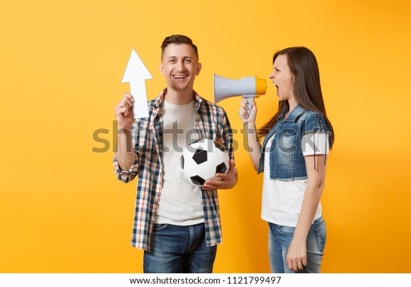 Happy fun expessive couple woman man football fans screaming, cheer up support team with soccer ball, white up arrow, megaphone isolated on yellow background. Sport family leisure lifestyle concept