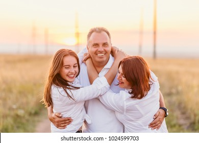 happy fun family in white shirts at sunset. family of three hugs in the field