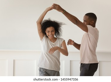 Happy funky young african american romantic couple holding hands dancing laughing at home, carefree active millennial black husband and wife wearing pajamas having fun bonding enjoy dance in bedroom