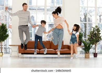 Happy funny active family with cute little kids son daughter holding hands jumping in living room, carefree parents and small children having fun flying in air laughing dancing together at home