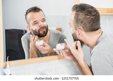 Happy funny adult guy applying moisturizer cream for male skin care. Man in front of bathroom mirror with anty aging lotion on face.