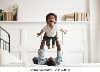 Photo of Happy funny african american kid boy flying in fathers arms looking at camera in bedroom, loving family single black dad holding lifting cute little child son playing plane bonding having fun on bed