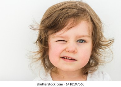 Happy funny baby eyewink isolated on white background. Beautiful close portrait of a girl winking with blue eyes