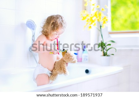 Happy funny baby girl wearing a diaper brushing her teeth and playing with her teddy bear toy and a toothbrush in a bathtub after shower in sunny white bathroom with window