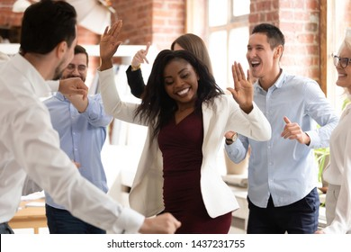 Happy funny black business woman with diverse team coworkers enjoy victory dance concept in office, multiracial friendly workers group dancing celebrate success having fun at corporate party together