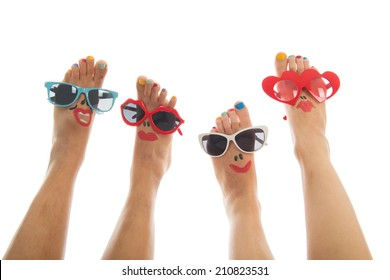 Happy and funny black and caucasian summer feet with colorful nail polish and sunglasses