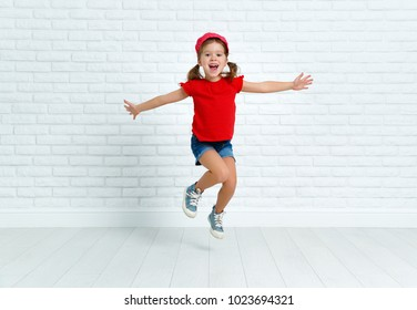 happy funny child girl jumping around empty wall
