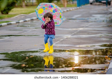 Happy funny child girl with multicolored umbrella jumping puddles in rubber boots and laughing