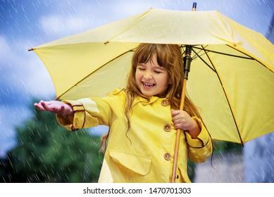 Happy funny child girl with umbrella
