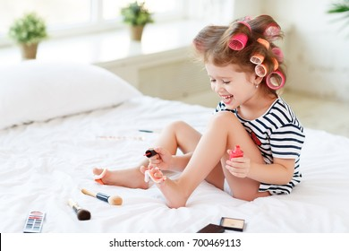 Happy funny child little girl with hair curlers does a pedicure, paints nails and laughs