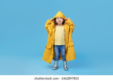 Happy funny child posing on blue studio background. Girl is wearing yellow waterproof raincoat and rubber boots. Weather forecast concept