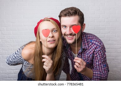 A happy funny couple in love enjoys Valentine's Day. A man with a beard and a woman with blond long hair. Paper red hearts. Loft style.