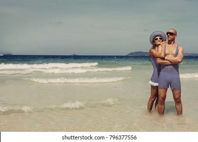 Happy funny couple in retro swimsuit on the beach