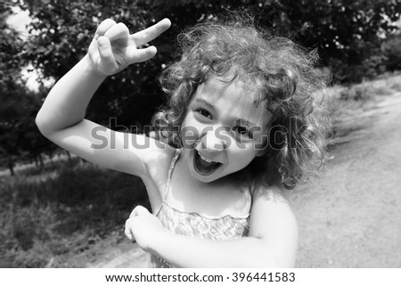 c0cea1c70 Happy, funny, crazy little girl having fun outdoors in the summer. Adorable,