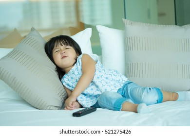 Happy Funny cute little asian girl holding a remote control and watching tv on her bed alone.