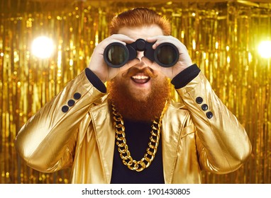 Happy funny extravagant man in shiny golden jacket and huge gold chain holding binoculars, looking for holiday deal, festive sale, special offer, discount, surprise, gift, present or showbiz casting