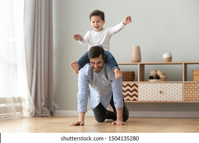 Happy funny family excited little boy playing with father at home, young dad crawling on floor carrying cute small child son on back giving kid piggyback ride having fun spending time together